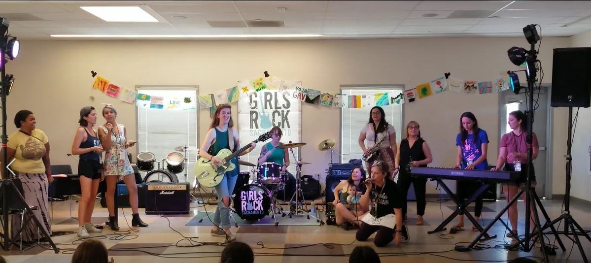 Girls playing a variety of instruments and singing in a jam session at Girls Rock Sacramento Teen Camp, July 2019