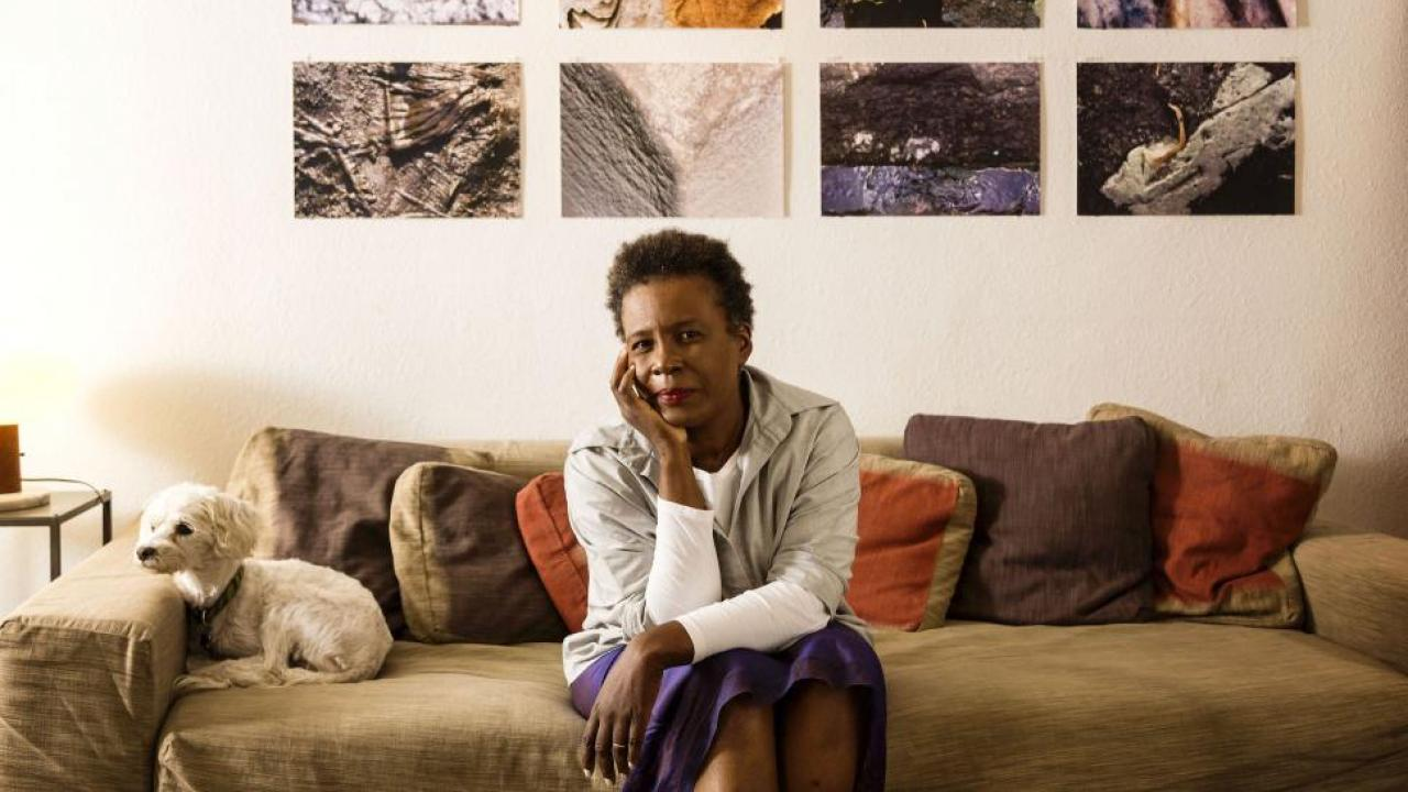 Portrait of Claudia Rankine sitting on couch with her dog
