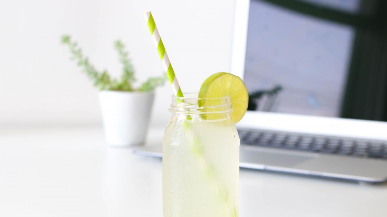 Glass of lemonade with a laptop in the background
