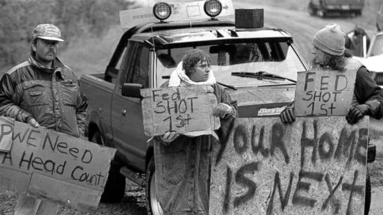 "Black and white photo of Ruby Ridge protesters. One holds a sign reading ""YOUR HOME IS NEXT"""