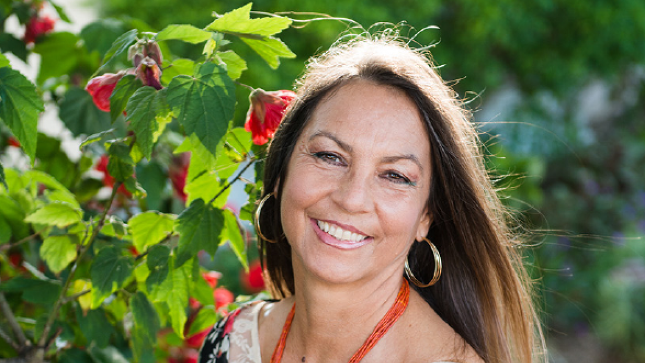 headshot of Dina Gilio-Whitaker near a flowering plant