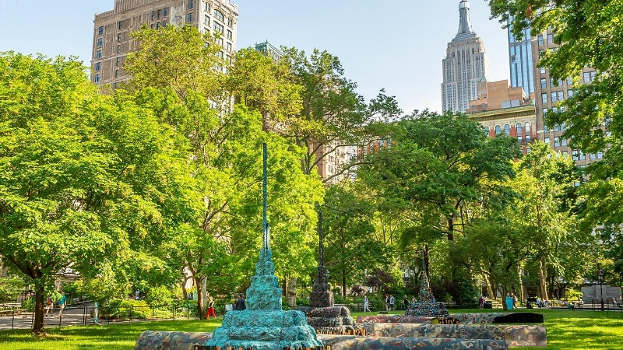 multicolored sculpture in an NYC park with empire state building in the background
