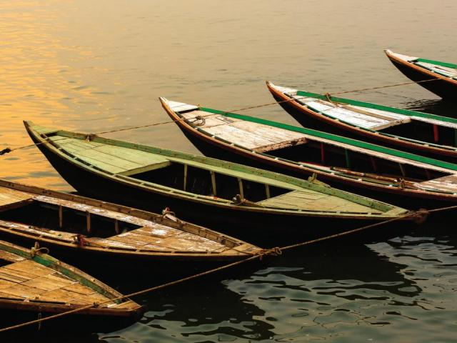 Cover image from Ganges: line of boats tied together on a river