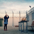 Still from Midnight Traveler: a child stands in an enclosure surrounded by barbed wire, taking a video with a cell phone.